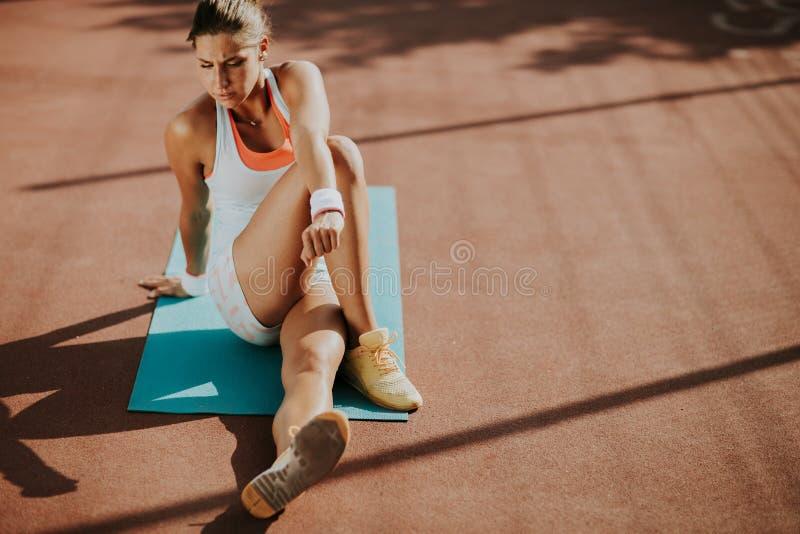 Νέα γυναίκα που παίρνει την άσκηση στοκ φωτογραφίες