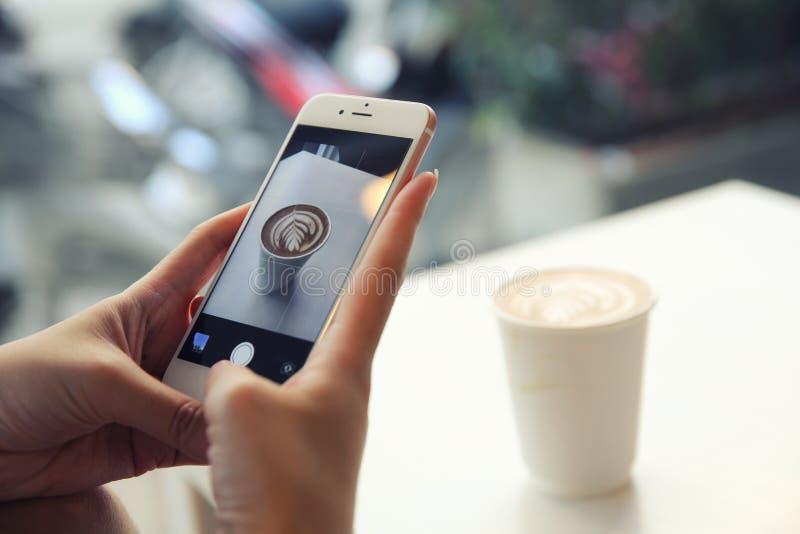 Νέα γυναίκα που παίρνει την εικόνα καφέ με το smartphone στοκ εικόνα με δικαίωμα ελεύθερης χρήσης