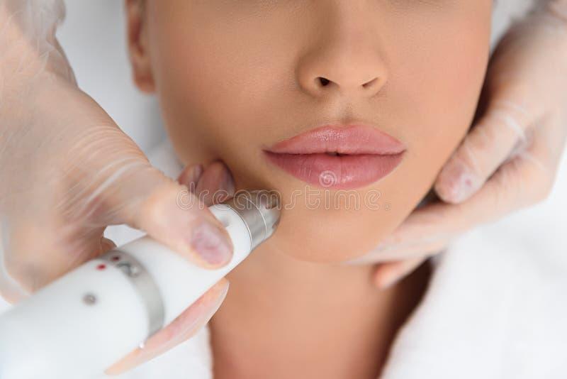 Νέα γυναίκα που παίρνει την καλλυντική αποφλοίωση του δέρματος στοκ εικόνες