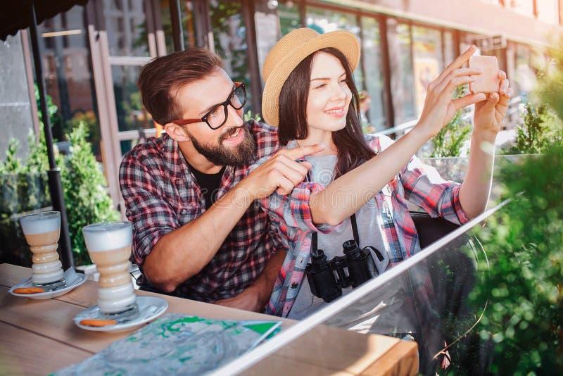 Νέα γυναίκα που παίρνει τις εικόνες που χρησιμοποιούν το τηλέφωνο Το άτομο κάθεται πίσω από το της και δείχνει προς τα εμπρός Περ στοκ εικόνες με δικαίωμα ελεύθερης χρήσης