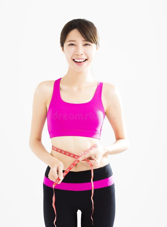 Νέα γυναίκα που παίρνει τις μετρήσεις του σώματός της στοκ εικόνες με δικαίωμα ελεύθερης χρήσης