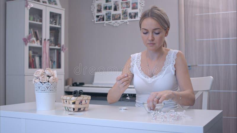 Νέα γυναίκα που παίρνει τις χάντρες για να κάνει το κόσμημα στοκ εικόνα με δικαίωμα ελεύθερης χρήσης