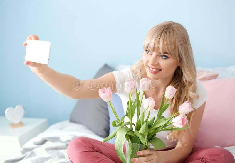 Νέα γυναίκα που παίρνει selfie με την ανθοδέσμη τουλιπών στην κρεβατοκάμαρα στοκ φωτογραφίες με δικαίωμα ελεύθερης χρήσης