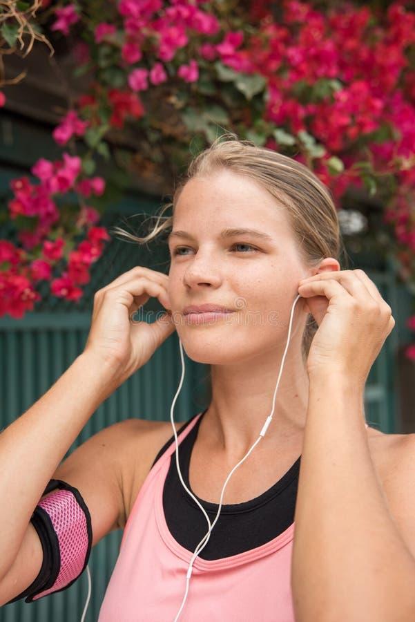Νέα γυναίκα που παρεμβάλλει τα τηλέφωνα αυτιών στα αυτιά της στοκ φωτογραφίες