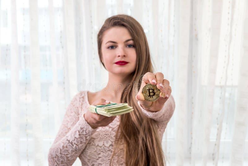 Νέα γυναίκα που παρουσιάζει δέσμη των δολαρίων και του χρυσού bitcoin στοκ φωτογραφία