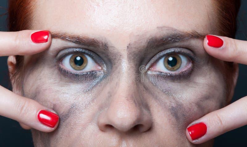 Νέα γυναίκα που παρουσιάζει μάτια της στην κινηματογράφηση σε πρώτο πλάνο στοκ φωτογραφία