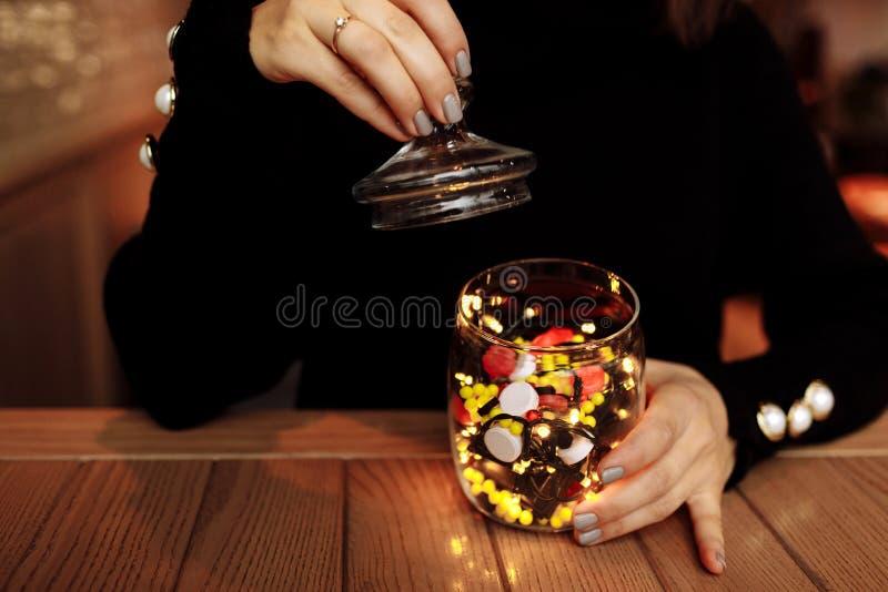 Νέα γυναίκα που παρουσιάζει μπουκάλι της ιατρικής Διαφορετικό ιατρικό χύσιμο καψών από ένα γυαλί η έννοια βρίσκεται καθορισμένο σ στοκ φωτογραφία