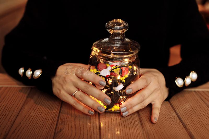 Νέα γυναίκα που παρουσιάζει μπουκάλι της ιατρικής Διαφορετικό ιατρικό χύσιμο καψών από ένα γυαλί η έννοια βρίσκεται καθορισμένο σ στοκ εικόνες