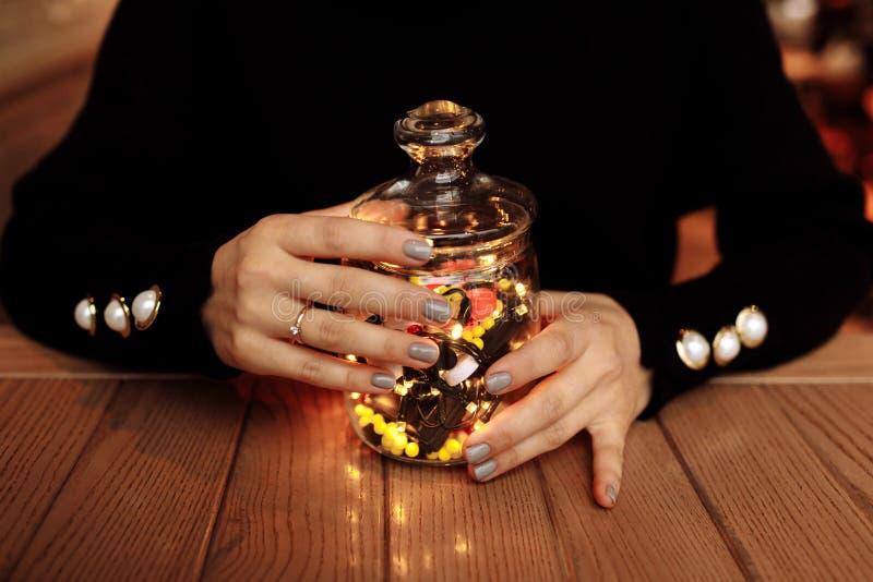 Νέα γυναίκα που παρουσιάζει μπουκάλι της ιατρικής Διαφορετικό ιατρικό χύσιμο καψών από ένα γυαλί η έννοια βρίσκεται καθορισμένο σ στοκ φωτογραφία με δικαίωμα ελεύθερης χρήσης