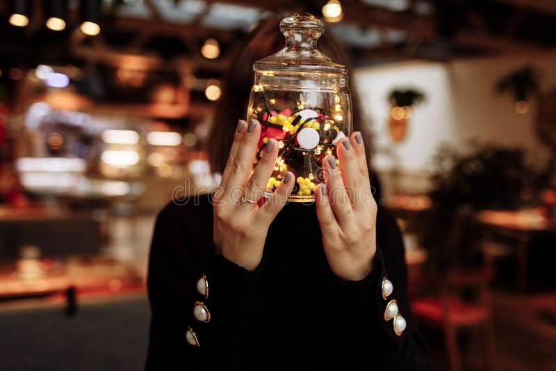 Νέα γυναίκα που παρουσιάζει μπουκάλι της ιατρικής Διαφορετικό ιατρικό χύσιμο καψών από ένα γυαλί η έννοια βρίσκεται καθορισμένο σ στοκ εικόνες με δικαίωμα ελεύθερης χρήσης