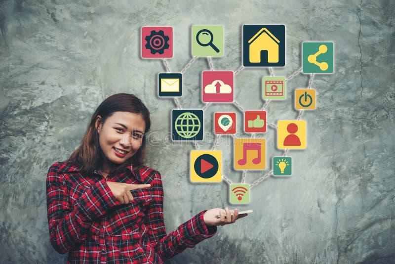 Νέα γυναίκα που παρουσιάζει στο σύγχρονο smartphone με το κοινωνικό ολοκληρωμένο κύκλωμα μέσων στοκ φωτογραφίες με δικαίωμα ελεύθερης χρήσης