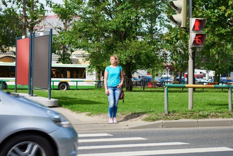 Νέα γυναίκα που περιμένει το πράσινο σήμα στοκ φωτογραφία