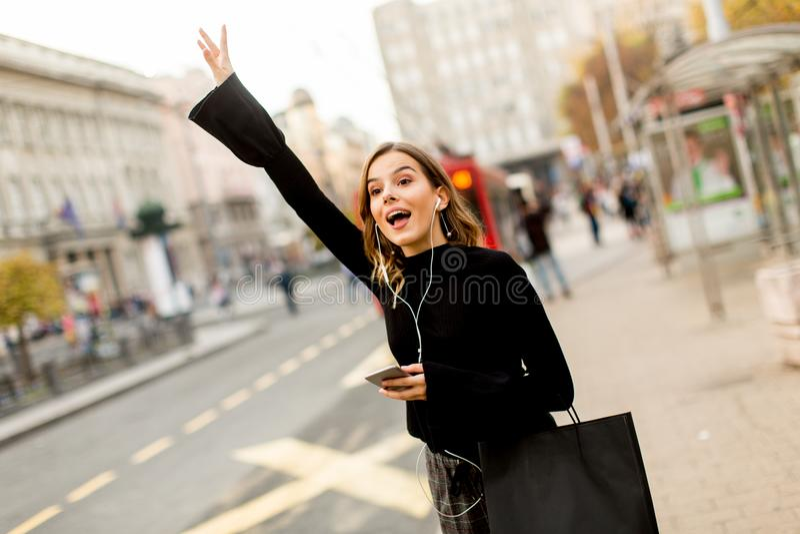 Νέα γυναίκα που περιμένει το ταξί ή το λεωφορείο στην οδό στην πόλη στοκ εικόνες