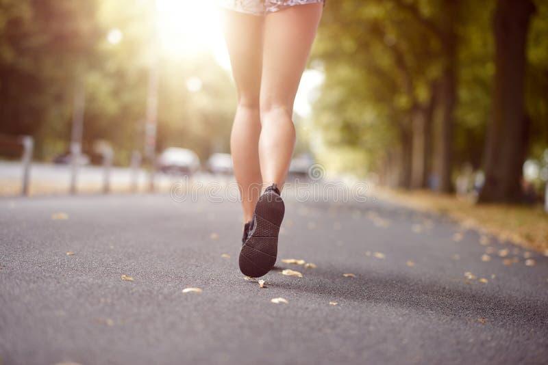 Νέα γυναίκα που περπατά ή που κάτω από μια οδό φθινοπώρου στοκ εικόνες