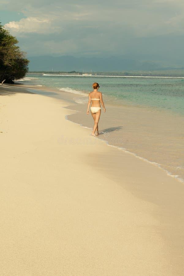 Νέα γυναίκα που περπατά κατά μήκος της τροπικής παραλίας στοκ εικόνα με δικαίωμα ελεύθερης χρήσης