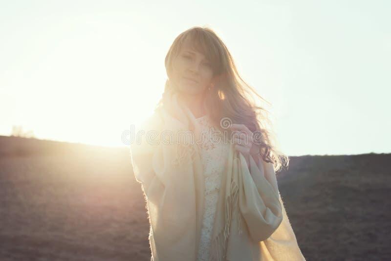 Νέα γυναίκα που περπατά στην παραλία κάτω από το φως ηλιοβασιλέματος, στοκ εικόνα