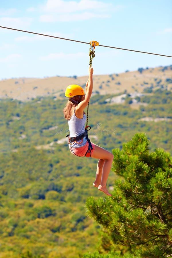 Νέα γυναίκα που πετά κάτω στο zipline στο βουνό, ακραίος αθλητισμός στοκ εικόνα με δικαίωμα ελεύθερης χρήσης
