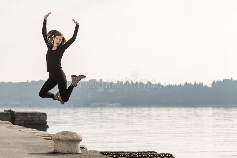 Νέα γυναίκα που πηδά για τη χαρά επάνω από έναν στυλίσκο στοκ εικόνα με δικαίωμα ελεύθερης χρήσης