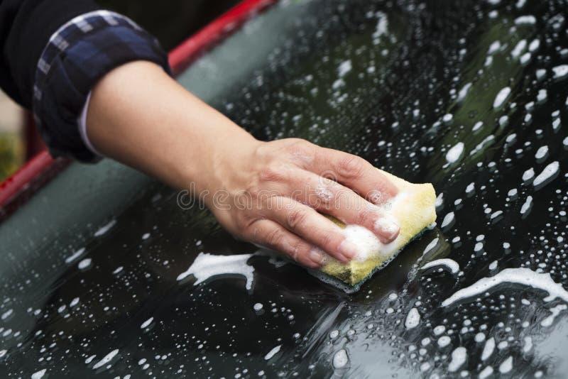 Νέα γυναίκα που πλένει ένα αυτοκίνητο στοκ εικόνες με δικαίωμα ελεύθερης χρήσης