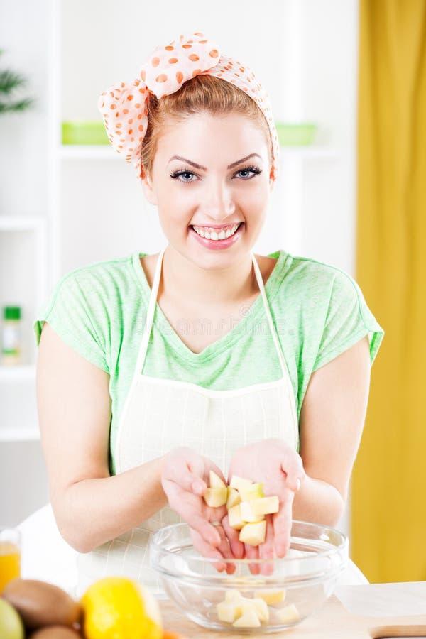 Νέα γυναίκα που προετοιμάζει τη σαλάτα φρούτων στοκ φωτογραφία με δικαίωμα ελεύθερης χρήσης