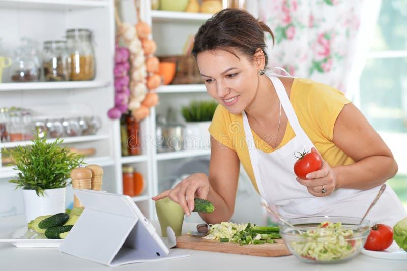 Νέα γυναίκα που προετοιμάζει το γεύμα στην κουζίνα στοκ εικόνα με δικαίωμα ελεύθερης χρήσης