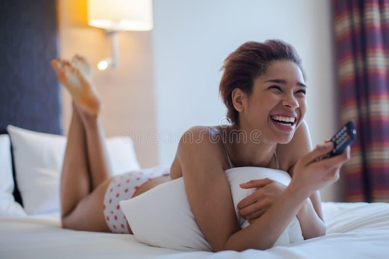 Νέα γυναίκα που προσέχει τη TV στο δωμάτιο στοκ φωτογραφία