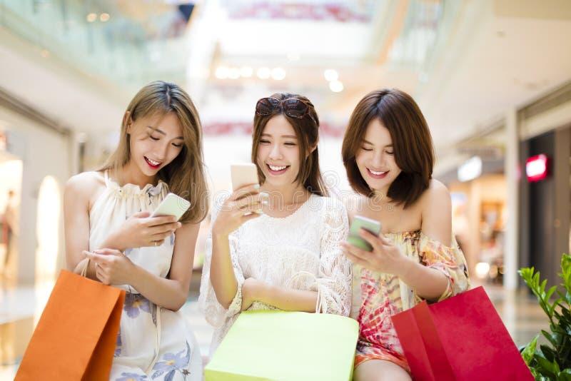 νέα γυναίκα που προσέχει το έξυπνο τηλέφωνο στη λεωφόρο αγορών στοκ εικόνα με δικαίωμα ελεύθερης χρήσης
