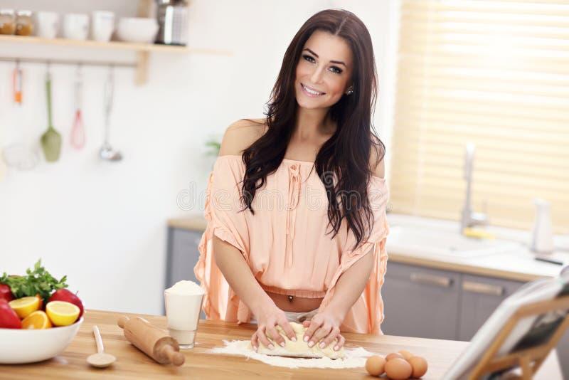 Νέα γυναίκα που προσπαθεί να κάνει το pierogi στην κουζίνα στοκ φωτογραφίες