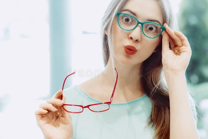 Νέα γυναίκα που προσπαθεί στα διαφορετικά ζευγάρια eyeglasses στοκ εικόνες