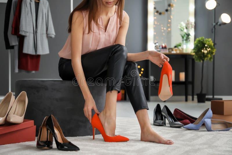 Νέα γυναίκα που προσπαθεί στα παπούτσια στοκ φωτογραφία