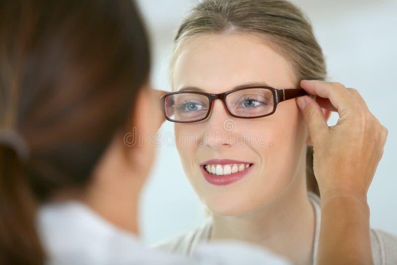 Νέα γυναίκα που προσπαθεί eyeglasses στο οπτικό κατάστημα στοκ εικόνα
