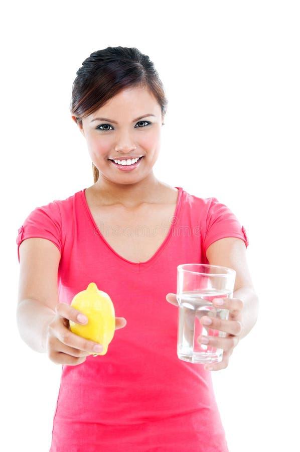 Νέα γυναίκα που προσφέρει το λεμόνι και το ύδωρ στοκ φωτογραφία