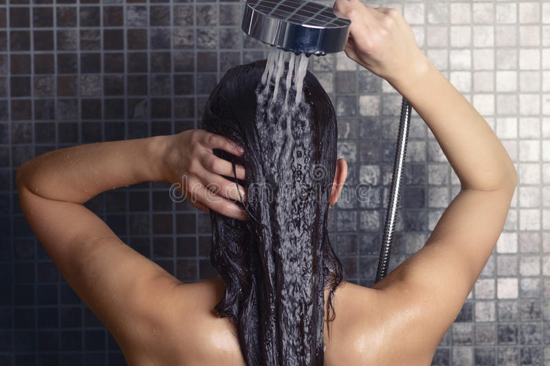 Νέα γυναίκα που πλένει την μακρυμάλλη κάτω από το ντους στοκ φωτογραφία