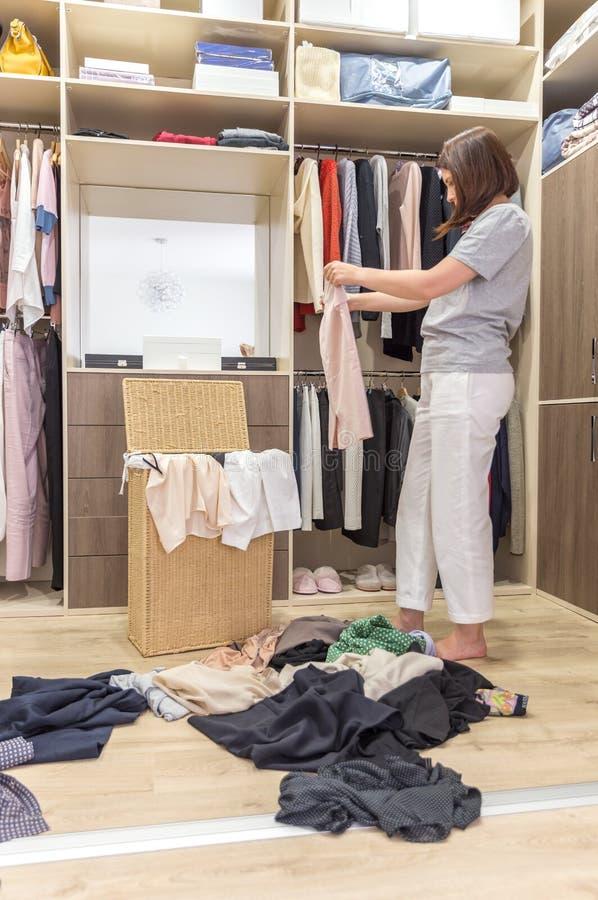 Νέα γυναίκα που ρίχνει τα ενδύματα στον περίπατο στο ντουλάπι Βρωμίστε στην ντουλάπα και το βεστιάριο στοκ φωτογραφίες