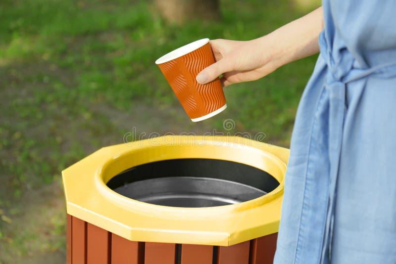 Νέα γυναίκα που ρίχνει το πλαστικό φλυτζάνι στο δοχείο απορριμάτων υπαίθρια στοκ φωτογραφία με δικαίωμα ελεύθερης χρήσης