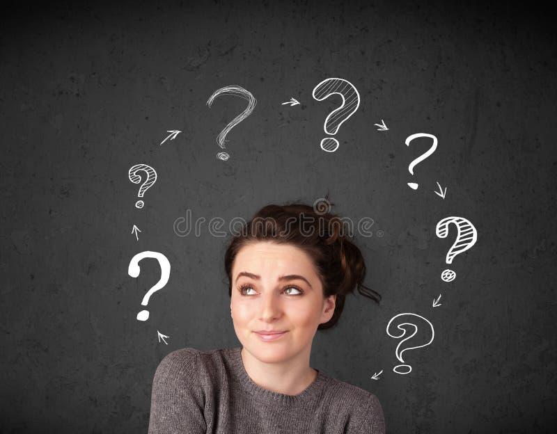 Νέα γυναίκα που σκέφτεται με την κυκλοφορία ερωτηματικών γύρω από το χ της στοκ εικόνα