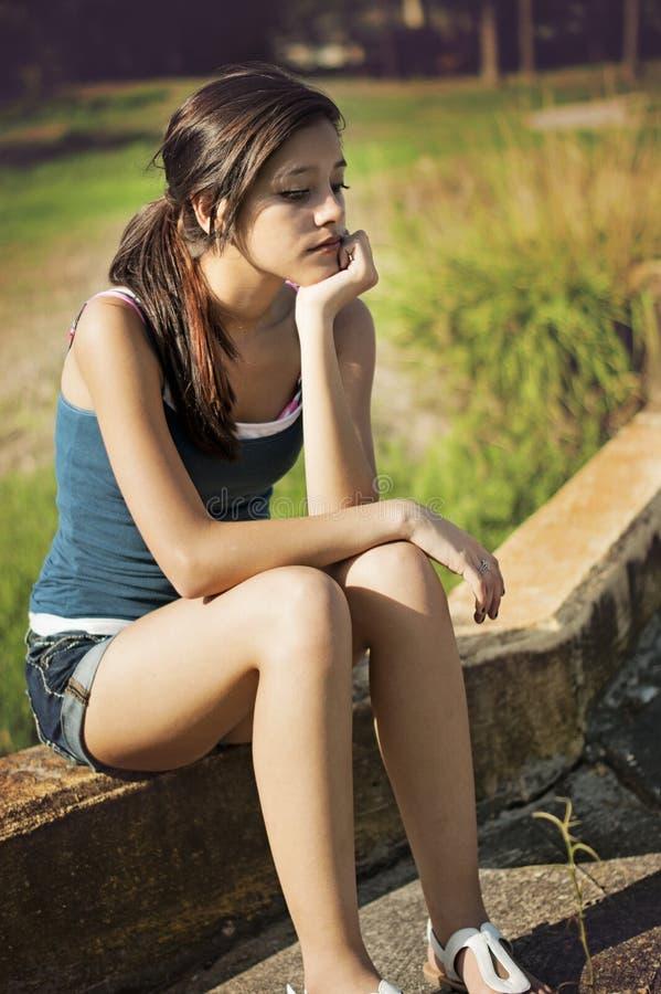 Νέα γυναίκα που σκέφτεται σε ένα πάρκο στοκ φωτογραφία με δικαίωμα ελεύθερης χρήσης