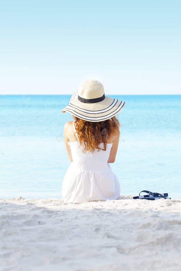 Νέα γυναίκα που σκέφτεται την προσοχή της θάλασσας στοκ εικόνα