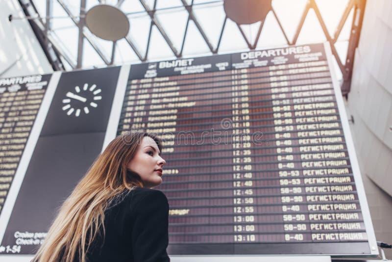 Νέα γυναίκα που στέκεται ενάντια στον πίνακα βαθμολογίας πτήσης στον αερολιμένα στοκ φωτογραφία με δικαίωμα ελεύθερης χρήσης
