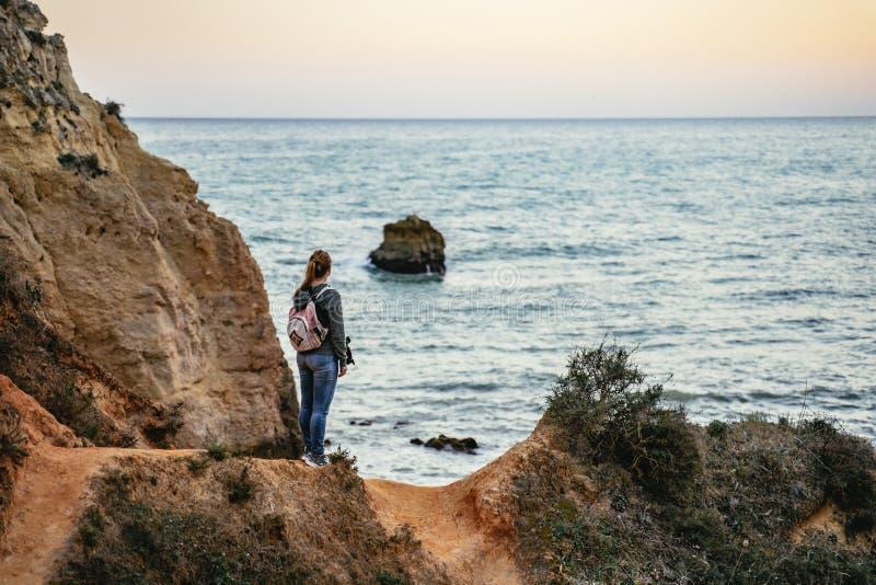 Νέα γυναίκα που στέκεται θαυμάζοντας μια ωκεάνια άποψη στοκ εικόνες