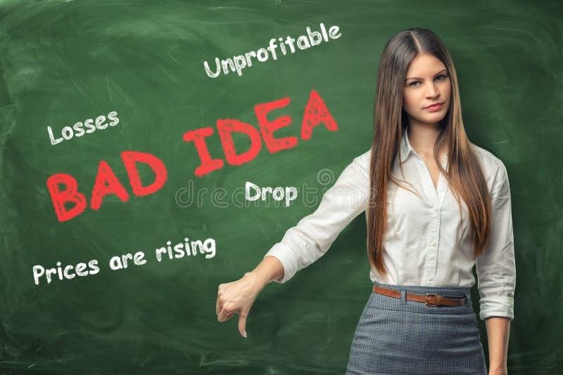 Νέα γυναίκα που στέκεται κοντά στη μεγάλη κόκκινη κακή ιδέα ` λέξεων ` στοκ φωτογραφία με δικαίωμα ελεύθερης χρήσης