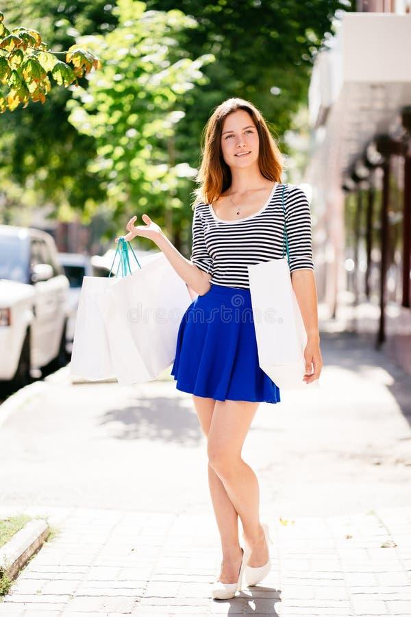 Νέα γυναίκα που στέκεται με τις τσάντες αγορών, χαμόγελο στοκ φωτογραφία