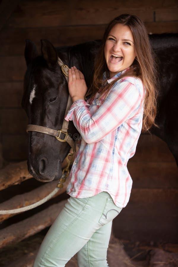 Νέα γυναίκα που στέκεται με το μαύρα άλογο και τα γέλιά της στοκ εικόνες