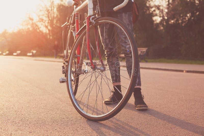 Νέα γυναίκα που στέκεται με το ποδήλατο στο ηλιοβασίλεμα στοκ φωτογραφία με δικαίωμα ελεύθερης χρήσης