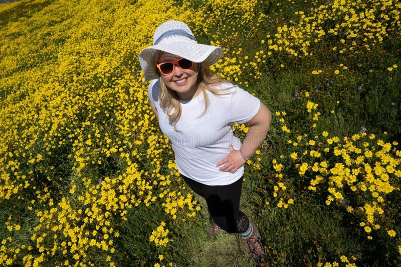 Νέα γυναίκα που στέκεται σε έναν κίτρινο τομέα wildflower, που φορά ένα άσπρο καπέλο ήλιων αχύρου Έννοια για τις εποχιακές αλλεργ στοκ φωτογραφίες με δικαίωμα ελεύθερης χρήσης