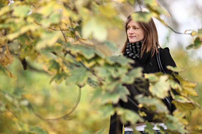 Νέα γυναίκα που στέκεται σε ένα πάρκο στοκ φωτογραφία