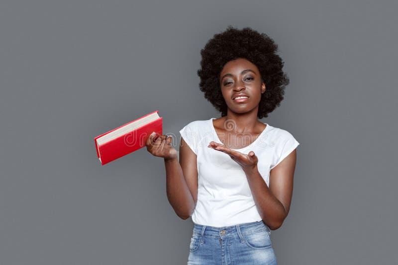 Νέα γυναίκα που στέκεται σε γκρίζο με το βιβλίο που φαίνεται κάμερα αναιδής στοκ φωτογραφίες με δικαίωμα ελεύθερης χρήσης