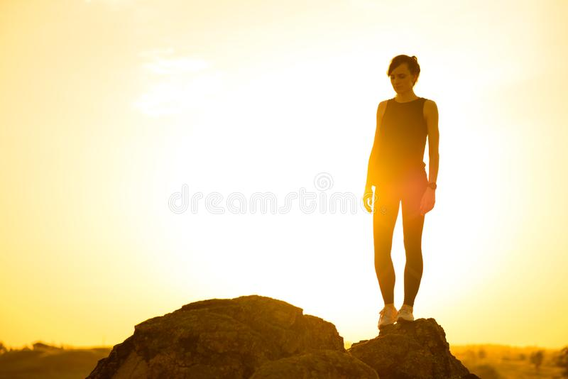 Νέα γυναίκα που στέκεται στο βράχο στο καυτό όμορφο θερινό ηλιοβασίλεμα Περιπέτεια και υγιής ενεργός έννοια Lifesyle στοκ εικόνες