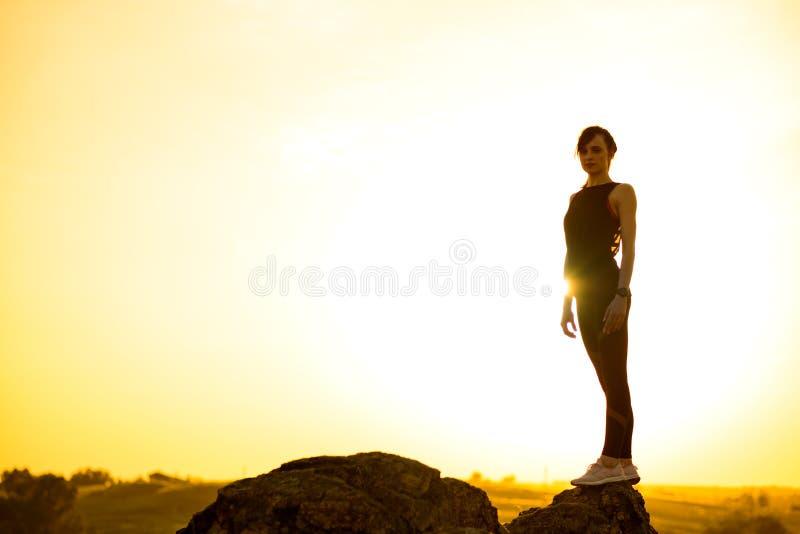 Νέα γυναίκα που στέκεται στο βράχο στο καυτό όμορφο θερινό ηλιοβασίλεμα Περιπέτεια και υγιής ενεργός έννοια Lifesyle στοκ εικόνες με δικαίωμα ελεύθερης χρήσης