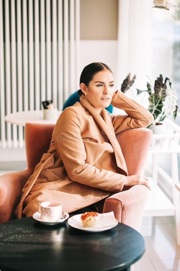 Νέα γυναίκα που στηρίζεται με το φλυτζάνι του τσαγιού στη καφετερία στοκ εικόνες